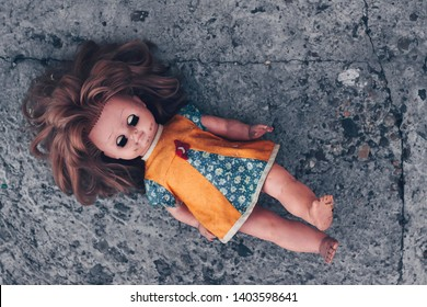 Old dirty doll with her eyes closed on concrete floor. The concept of a bygone childhood, loneliness and abandoned