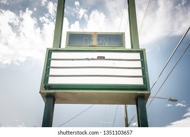 An old, dirty and empty backlit box letter sign board standing on the roadside.