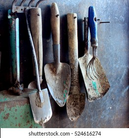 old dirty farm metal garden tools as shovels and rakes hanging on the wall on nails