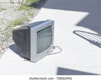 The old dirty gray TV is on the street