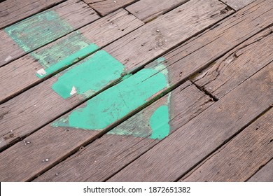 Old dirty green arrow was on the wooden floor.