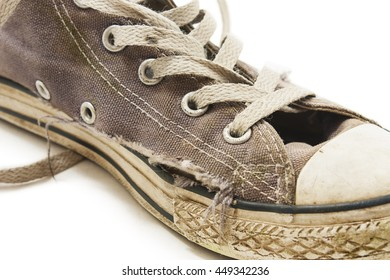 Old and dirty grey canvas sneakers. Isolated on white background