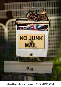 Old and dirty mailbox with text NO JUNK MAIL full of junk mail and newspapers with spiderwebs in front of fence