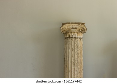 old dirty marble decorative threaded column antique ancient Greek architecture object indoor museum exhibit on white wall background, empty copy space for text or inscription