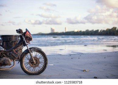 Old and dirty motercycle parking on the beach at morning ready to start working