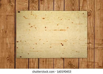 Old dirty paper sheet on brown wooden textured board