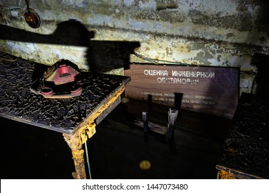"""Old dirty phone on decaying table inside of flooded fallout shelter. Illuminated by flashlight. Translation: """"Оценка инженерной обстановки"""" - Evaluation of the engineering situation."""