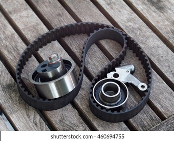 old dirty rustic used long distance expired car automotive timing belt, teethed belt for diesel engine removed together with tension automatic adjusted pulley bearing set laying on wooden garage table