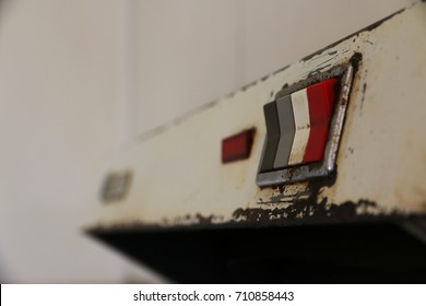 An old, dirty and rusty front of a metallic exhaust hood, with its worn out switches. The once modern white kitchen has decayed over time. The red antique switch is a concept about dangerous decisions