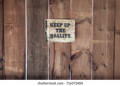An old dirty sign posted on a wooden wall.
