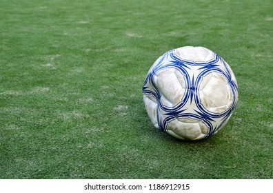 Old, dirty, tattered, flabby soccer ball on background of green grass. Football ball on green field of the stadium training playground. Copy space, place for text