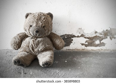 A old and dirty Teddy bear is sitting against a white concrete wall. vintage processing