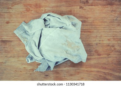 Old dirty torn rag on a dirty wooden desk background. Cleaning rag.