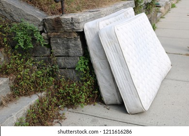 Old discarded mattress left outside in urban alleyway