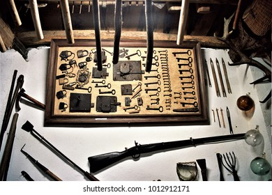 old display of iron keys and old padlocks and locks and an old hunting shotgun, Galician ethnographic museum, tools of the old trade of blacksmith and hunter,
