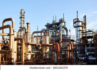 Old distillation column towers and reactors under blue evening sky background at chemical plant. Exterior of silver metal rusty enterprise with copyspace.
