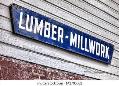 Old and distressed lumber millwork antique advertising enamel sign hanging on a vintage lumberyard wood clapboard wall