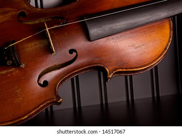 Old distressed violin with one string, leaning against black beadboard wall