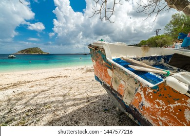 Old disused and abandoned rowing boat on the beach in Agios Nikolaos port in summer, Zante Island, Greece