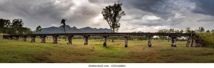 An old disused rail bridge with Mount Walsh in the background.