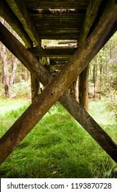 Old disused timber railway bridge in bushland near Daylesford, Victoria, Australia