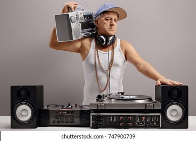 Old DJ with a boombox and musical equipment against a gray wall