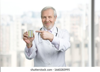 Old doctor pointing at pack of capsules. Concept of pills advertisement, recommending drugs medicine. Bright background.