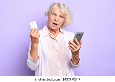 old doctor with surprised expression holding mobile phone and credit card. old woman cannot understand how she hasspend money, lost money. watch out, mobile fraudsters. isolated light blue background.