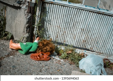 Old doll and red child sandal lying on the dirty ground near the gate. Child protection, safety, poverty concept