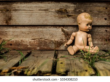 Old Doll Sitting Against Derelict Building.
