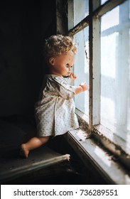The old doll stands by the window and looks out the window. The concept of loneliness, sadness, poverty. Horror, scary, Halloween.
