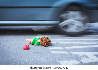 Old doll toy and red sandal in the middle of the road with car in motion in the background. Child abduction, missing children day concept