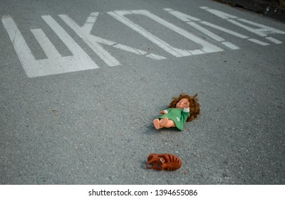 Old doll toy and red sandal in the middle of the road near school. Eastern Europe. On the road is written – School in Serbian. Child abduction, missing children day concept - Shutterstock ID 1394655086