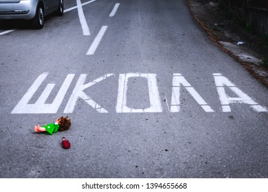 Old doll toy and red sandal in the middle of the road near school. Eastern Europe. On the road is written – School in Serbian. Child abduction, missing children day concept - Shutterstock ID 1394655668