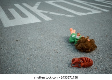 Old doll toy and red sandal in the middle of the road near school. Eastern Europe. On the road is written School in Serbian. Child abduction, missing children day concept - Shutterstock ID 1433571758