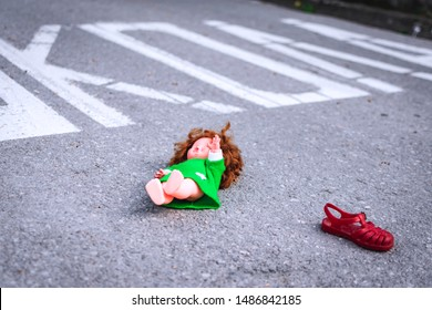 Old doll toy and red sandal in the middle of the road near school. Eastern Europe. On the road is written School in Serbian. Child abduction, missing children day concept - Shutterstock ID 1486842185