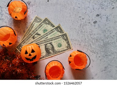 Old Dollar money with pumpkin bucket with Halloween decorations on marble pattern table
