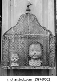 Old dolls heads in cage at flea market in France. Black and white.