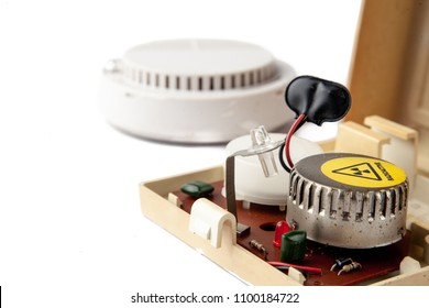 Old domestic smoke detector alarms on white background