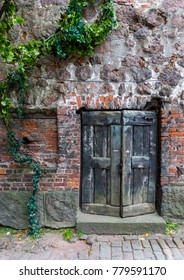An old door in brick wall and stone wall.