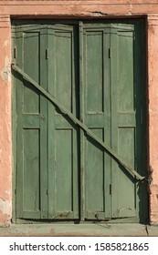 Old door. Door closed by a large hook. Decrepit green wooden door. Close-up.