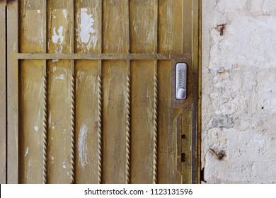 Old door with code lock and metal grid