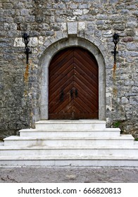 An old door on the background of an old stone wall and steps in Budva, Montenegro.
