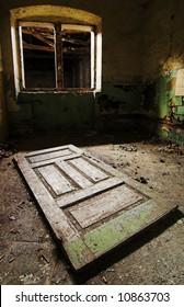 Old door on the floor and window without window-panes