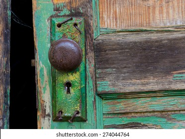 Old door and rusty keyhole with bent nails from a world war ii army barrack