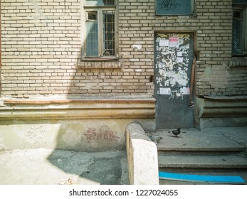 Old door with stairs on brick old wall. Zaporozhye, Ukraine, 25 August 2018.
