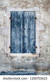 An old door with weathered blue paint is an old entrance to a winery in Gevrey-Chambertin in the Burgundy region of France.