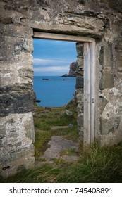 Old doorway of ruined house frames sea view beyond.