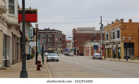 The old downtown section of a small city, dominated by brick buildings, is shown during a street level, daytime view.