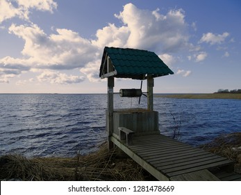 Old draw well on shore of lake. View of water through well gate. Paradox of water in the water. Concept of abundance of drinking water